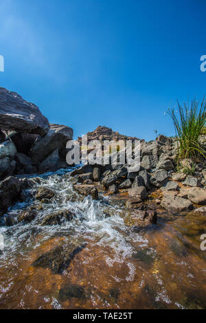 Water flowing from a river over some rocks in Hampi, India - Stock Image