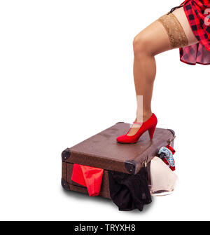 woman in red dress and nylon stockings standing her leg on a suitcase  isolated on white. legs closeup - Stock Image