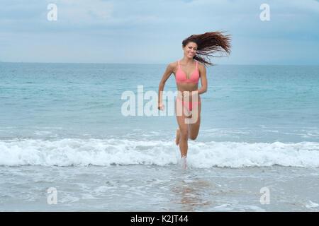 Attractive woman in bikini running at a beach - Stock Image