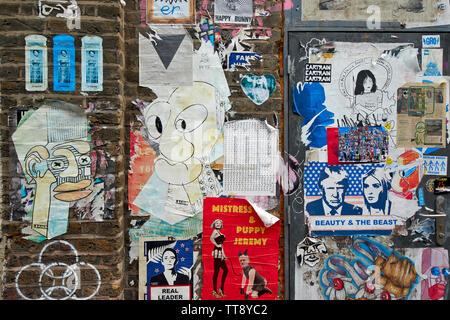 LONDON ENGLAND BRICK LANE POSTERS AND GRAFFITI ON AN OLD BRICK WALL - Stock Image