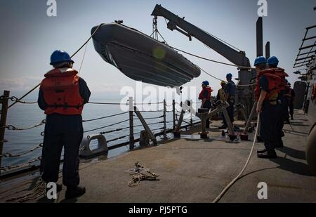 180825-N-UY653-057  BLACK SEA (Aug. 25, 2018) Sailors lower a rigid-hull inflatable boat from aboard the Arleigh Burke-class guided-missile destroyer USS Carney (DDG 64) Aug. 25, 2018. Carney, forward-deployed to Rota, Spain, is on its fifth patrol in the U.S. 6th Fleet area of operations in support of regional allies and partners as well as U.S. national security interests in Europe and Africa. (U.S. Navy photo by Mass Communication Specialist 1st Class Ryan U. Kledzik/Released) - Stock Image