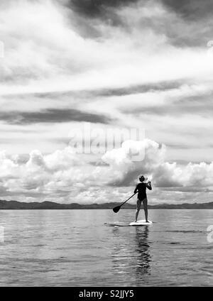 A young women stand up paddles. Tavarua, Fiji. - Stock Image
