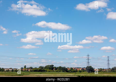 View over reed beds of the River Test estuary at Redbridge as it enters Southampton Water looking towards Totton with electricity pylons and lines - Stock Image