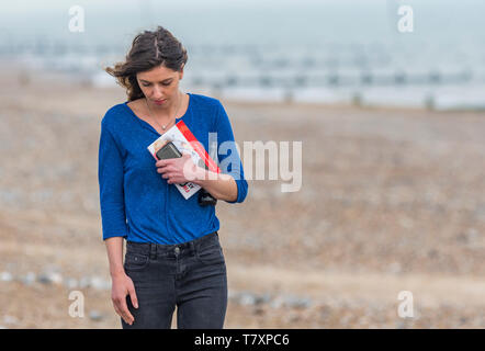 Young woman strolling alone while thinking on a beach in Spring. Lonely woman walking alone. Time to think concept. Loneliness concept. - Stock Image