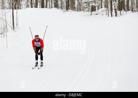A classic style skier tucks and glides downhill on the trail between Cable and Hayward Wisconsin during the American - Stock Image