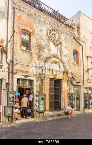 Taormina, Sicily - 22nd September 2017: Old building and shop on the Corso Umberto. This is the main street through the town. - Stock Image