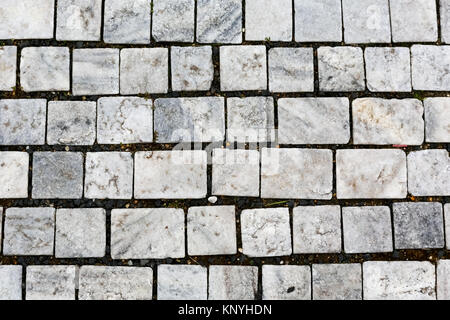 The bright sidewalk that is made of granite cobbles - Stock Image
