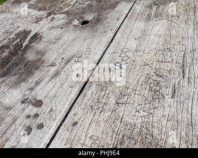Various initials carved into the top of a wooden picnic bench. Concept 'Leaving your mark'. - Stock Image