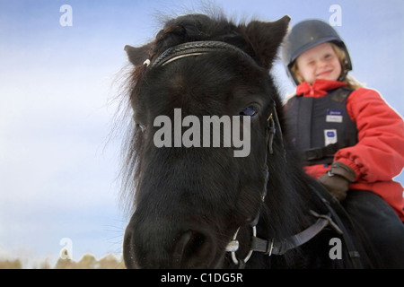 Young happy girl on a black pony. - Stock Image