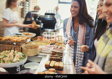 Smiling women friends at cafe - Stock Image