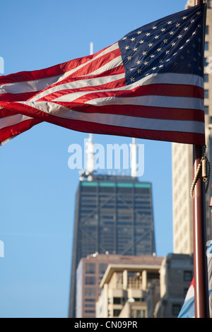 The stars and stripes wave in front of the Hancock Center, Chicago - Stock Image