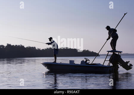 A silhouette of  a fly fisherman and a guide casting for redfish from a flats boat poling skiff in the fresh water marsh south of New Orleans, Louisia - Stock Image