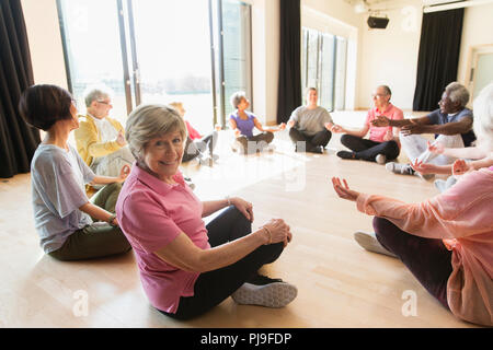 Portrait smiling active senior woman meditating in circle - Stock Image