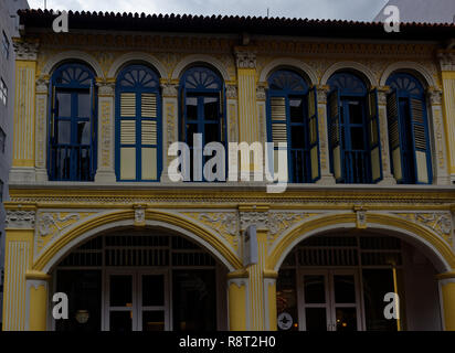 Blue window frames and yellow walls on a traditional Chinese shophouse in Purvis Street, Singapore - Stock Image