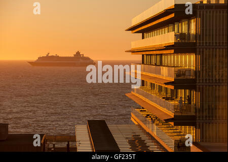 A cruise ship leaves Cádiz bay at sunset, while people enjoy the view from the terrace of the hotel 'Parador - Stock Image