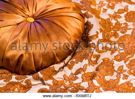 Gold coloured circle shaped luxurious pillow laying on a bed sheet with flower pattern. - Stock Image