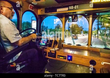 Miami Beach Florida Normandy Isle North Beach Loop free trolley bus public transportation onboard cabin night Hispanic man driver driving employee - Stock Image