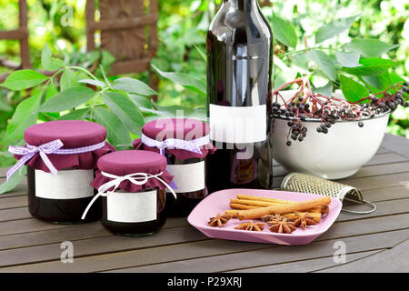 Homemade elderberry jelly and juice in a bottle and glass jars with elderberries on a wooden table outdoors in front of green leaves, copy space. - Stock Image