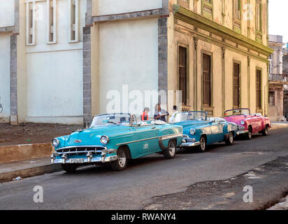 Colourful old American cars used as taxis in a dilapidated side street off El Malecon, Bahia de la Habana, Havana, capital of Cuba - Stock Image