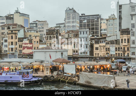Partial view of the Golden Horn seafront with the lit stalls of the Karaköy fish market by the water's - Stock Image