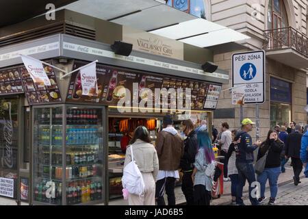 Customers queuing up outside Václavsky Gril, fast food kiosk, Prague, Czech Republic - Stock Image
