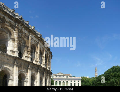 View at Arena of Nimes, Roman amphitheater, the court of Justice and the Church Sainte Perpetue in France - Stock Image