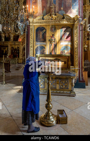 Woman lighting candle at Cathedral of the Dormition, Sergiev Posad Monastery, Russia - Stock Image