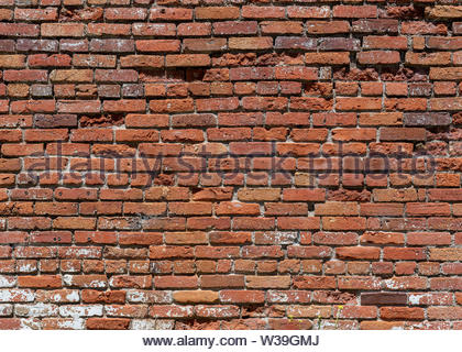 Old weathered brick wall partly with some bricks broken and others missing, seen from a distance, large copy space - Stock Image