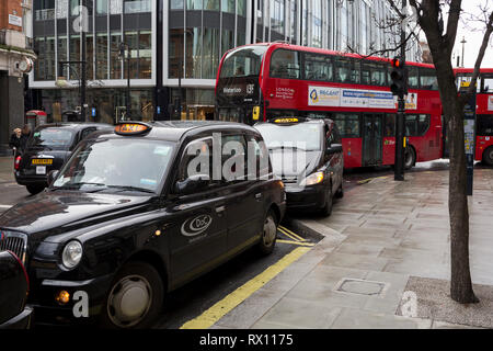 With engines running, traditional black cabs queue for fares, consequently blocking bus traffic outside the Selfridge's department store on Oxford Street, on 4th March 2019, in London England. - Stock Image