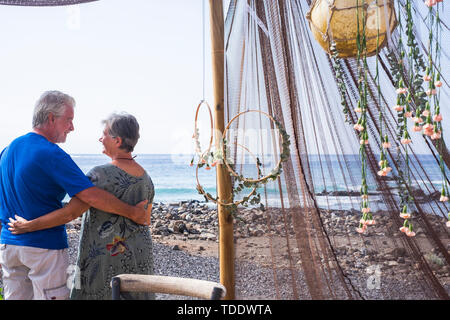 Happy retired lifestyle with couple of senior people hug and look eachother viewed from back - ocean and beach in background - vacation concept - Stock Image