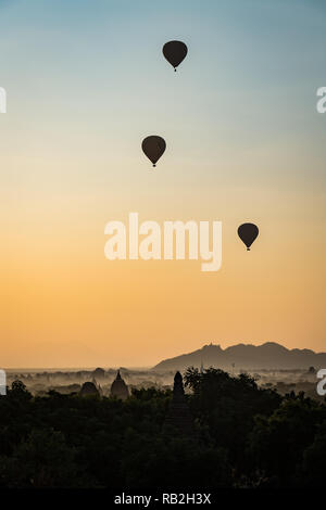Hot air balloons float above mist as sunrise highlights the temples of Bagan, Myanmar - Stock Image
