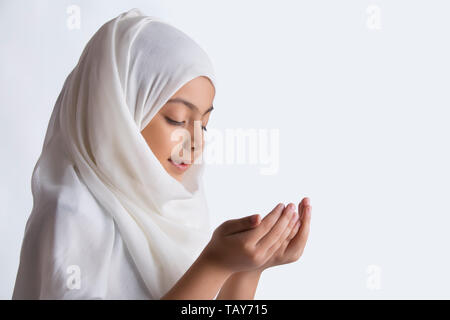 Young Muslim girl wearing hijab and praying with eyes closed - Stock Image