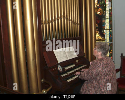woman playing organ in church - Stock Image