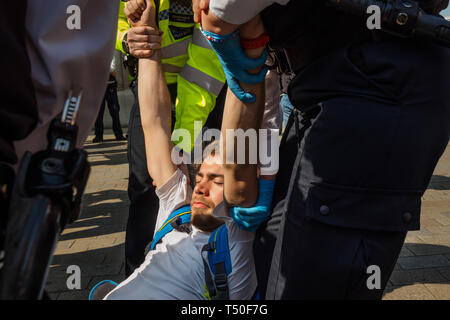 London, UK. 19th April 2019. Police drag away a person who has been arrested at at Extinction Rebellion's Sea of Protest after police surrounded the yacht and put a ring of officers around Oxford Circus. Police tried to persuade protesters to leave by threatening them with arrest. Later there were a number of arrests of protesters who refused to leave. A few tried to get the large crowd to protect the yacht, but XR organisers persuaded them not to physically oppose the police action. Peter Marshall/Alamy Live News - Stock Image