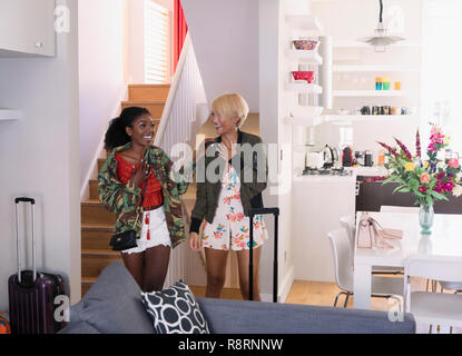 Excited young women friends arriving at house rental - Stock Image