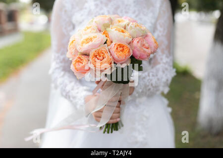 Hands of bride holding bouquet - Stock Image