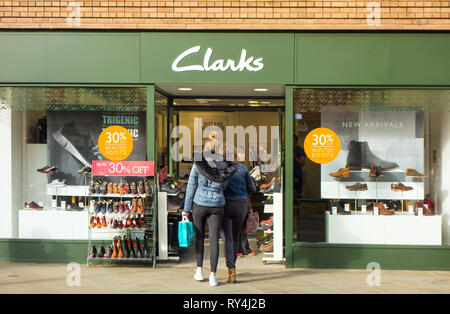 Women shoppers shopping and looking in the window of Clarks shoe shop - Stock Image