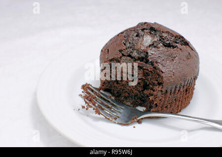 Partially Eaten Chocolate Muffin With A Fork On A White Background - Stock Image