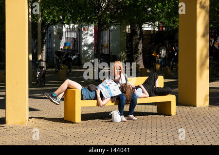 Three women tourists resting on a stone bench in the sun in Alameda de Hercules in Seville - Stock Image