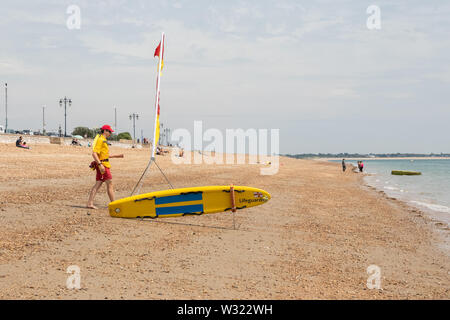 A lifeguard patrolling a British pebble beach with surfboard and red and yellow flags - Stock Image