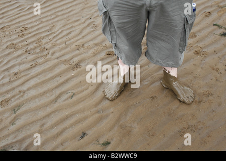 man s feet covered in wet sand - Stock Image