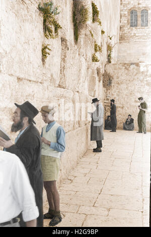 Wailing wall in Jerusalem in 1946 with locals praying and a British soldier taking a photograph in the background, - Stock Image