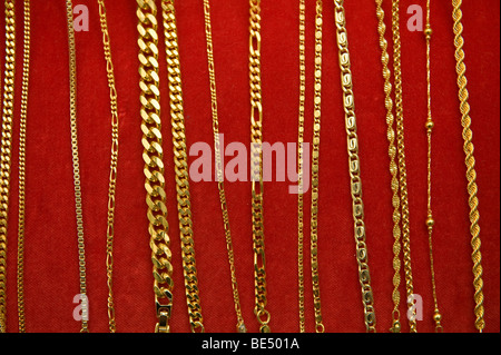 image of gold chain assortment on red velvet display board - Stock Image