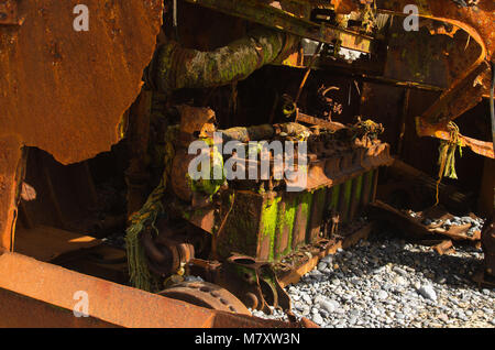 The big, old and rusted engine of a destroyed pusher boat wrecked at the beach. Vila Nova de Milfontes, Portugal. - Stock Image