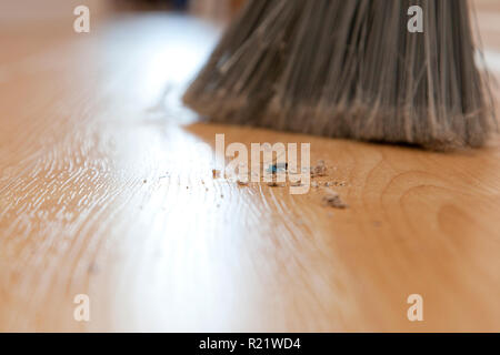 Close up of dirt and sweepings on the floor beside a broom - Stock Image