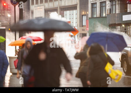 (Selective focus) Blurred people with umbrellas are crossing the 42nd street in Manhattan. Steam coming out from from the manholes in the background.  - Stock Image