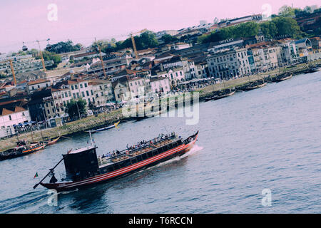 Porto, Portugal - April 28, 2019: Tourist boats on the Douro River at the famous UNESCO World Heritage Site of Cais Ribeira overlooking Gaia - Stock Image