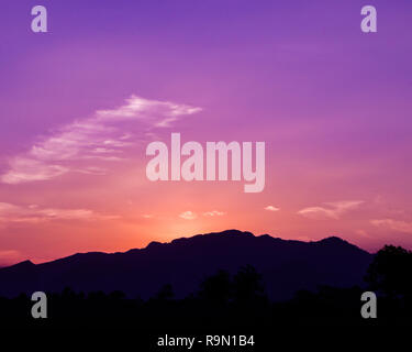 Silhouette mountains under beautiful vibrant sky - Stock Image