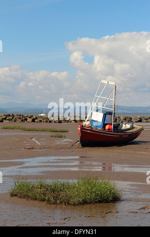 A red, white and blue fishing boat resting on the sands of Morecambe Bay during low tide. - Stock Image