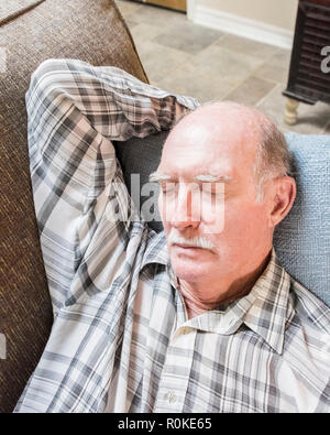 An old man wearing a plaid shirt taking a nap on a sofa. - Stock Image